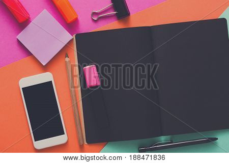 Creative minimal design, flat lay of workspace desk with stationery, mobile smart phone, blank black sketchbook with copy space. Template, mockup, objects