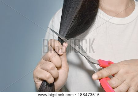 Woman asian going to cut her hair with scissors. Concepts - to change the image / broken heart / hair problems