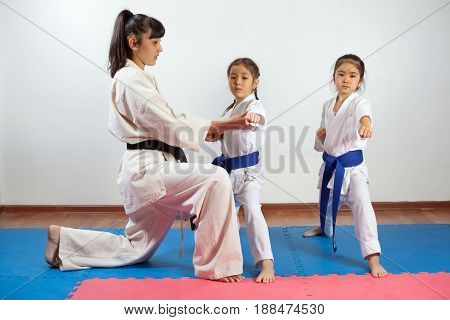 Coach woman showing martial art for children. Fighting position active lifestyle practicing fighting techniques