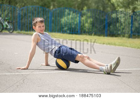 A Teenager In A T-shirt Is Sitting On A Ball Resting