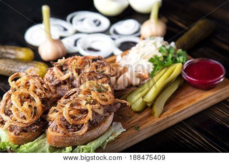 Meat sandwich with fried onions, marinated vegetables  and cranberry sauce