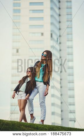 Mom and daughter in stylish clothes - jackets jeans and glasses