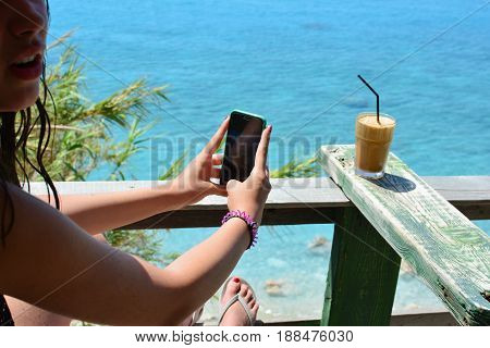 Young teenage girl refreshing in cafe with sea view ang photographing her ice coffee frappe by mobile phone