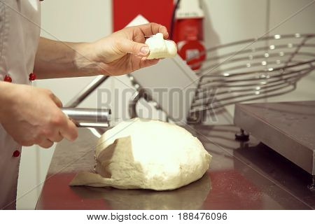 Cutting  dough in flour with a knife. Hands cutting dough