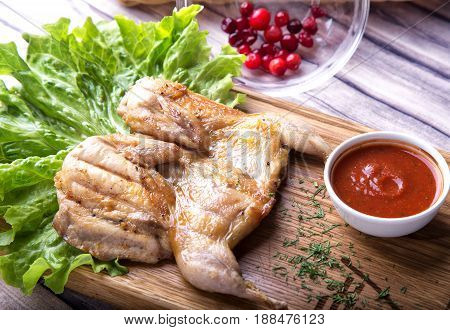 Roasted Quail with  cowberry sauce on the wood background