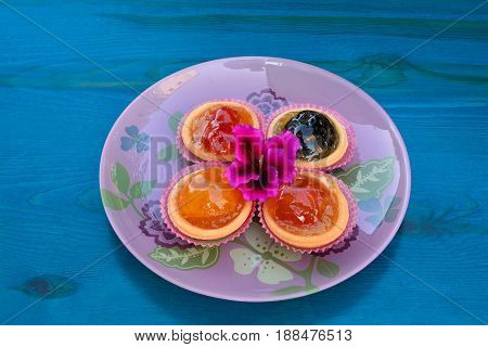 Punnets of dough filled in with various candied fruits served in pink glass plate on blue wooden table decorated with pink flower