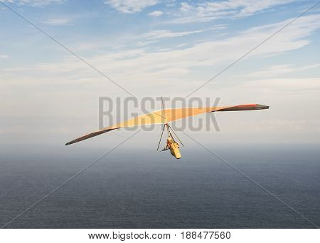Hang glider is soaring in a gliding flight into a cloudy sky over the ocean hanging on a harness below the wing