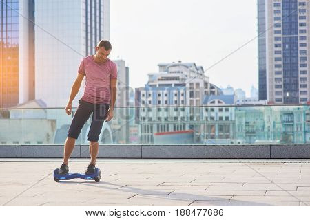 Guy on hoverboard, city background. Man outdoors at daytime. Era of technologies.