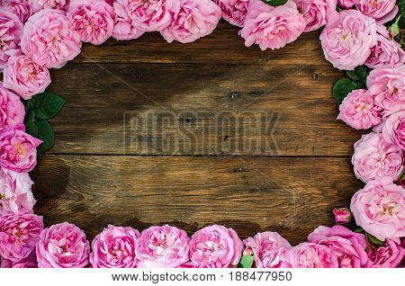 Floral Frame With Pink Rose Flowers On Wood Background. Place For Text, Top View.