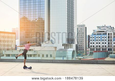Guy on hoverboard, city. Person with arms wide spread. The complete freedom.