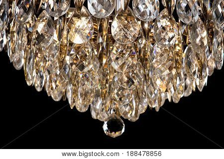 Large crystal chandelier detail isolated on black background. Luxury expensive chandelier for living room, Hall of celebration. Beautiful crystal decoration for the party