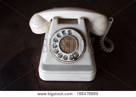 Old White Vintage Telephone, Phone Land  Or Landline With Dust, Circle Dialpad And Scratches On Wood