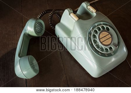 Old Green Vintage Telephone, Phone Land  Or Landline With Dust On Wooden Retro Desk. Vintage Desk Te