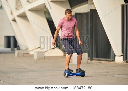Young man on hoverboard outdoors. Guy riding gyroscooter.