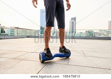 Legs on hoverboard, city background. Person riding blue gyroscooter.