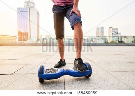 Male legs and hoverboard. Blue gyroscooter on city background. Gadget advertising ideas.
