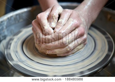 Master potter folded together hands sculpts a clay product on a potter's wheel. Hand skin stained with clay and wet