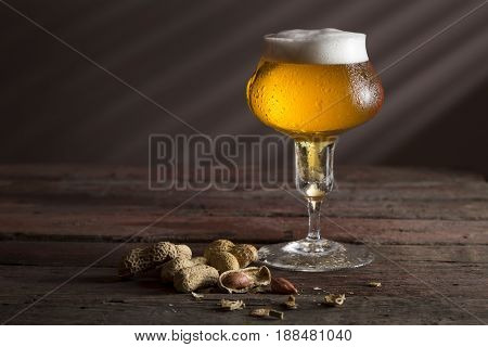Glass of cold pale beer with a bowl of peanuts on a rustic wooden table. Selective focus