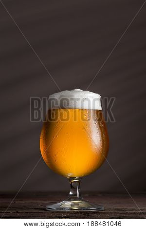 Glass of cold light unfiltered beer on a rustic wooden table