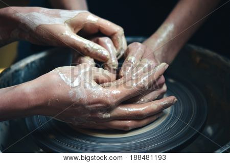 Two people mold a clay pot from white clay. Master potter teach from clay in workshop close-up