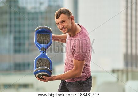 Man holding gyroboard. Person with a gadget outdoors. Hoverboard with improved battery capacity.