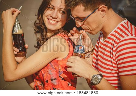 ODESSA, UKRAINE - OCTOBER 15, 2014: Close up of beautiful young smiling couple in love, hugging outdoors drinking cold Pepsi from glass bottles with straw.