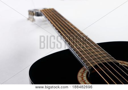 Part of a black Six-string classical acoustic guitar on white background.