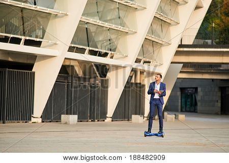 Businessman riding hoverboard. Guy with a tablet outdoors.