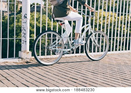 Closeup Of A Woman In A Jacket And Jeans Riding A City Bike