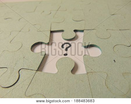 missing piece of a jigsaw puzzle with question mark