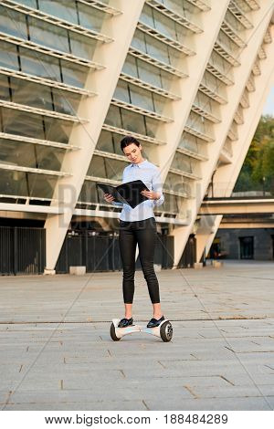 Woman looking into open folder. Young female riding hoverboard. Business research methods.