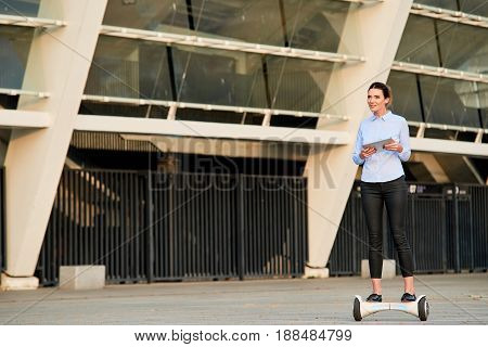 Woman with tablet riding hoverboard. Businesswoman in the street.