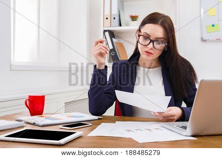 Paperwork. Serious business woman in formal wear sitting at wooden desk in modern office and reading report document. Concentrated female manager working on marketing strategy at workplace