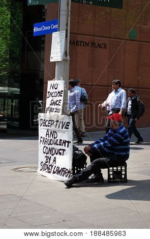 SYDNEY AUSTRALIA - OCTOBER 28 2013: A senior male person protests at Martin Place Sydney. His poster signs represent concept of unemployment economy stagnation and law firm misconduct