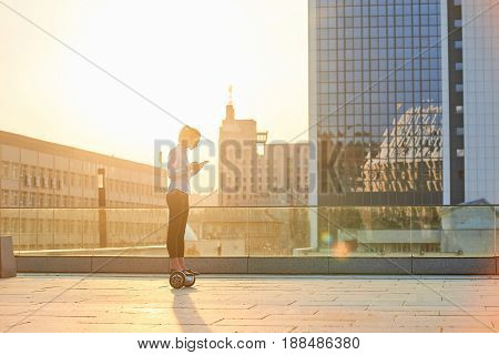 Businesswoman on sunny city background. Lady on hoverboard holding tablet. Business of the future.