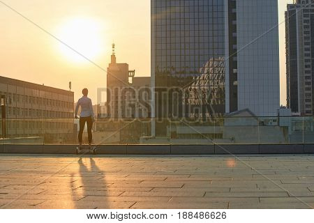 Woman on hoverboard, sunny city. Back view of person outdoors.