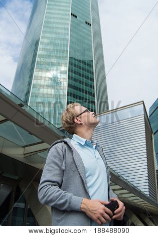 Young man with blond hair, wearing glasses looks up at the tall buildings of the business center.