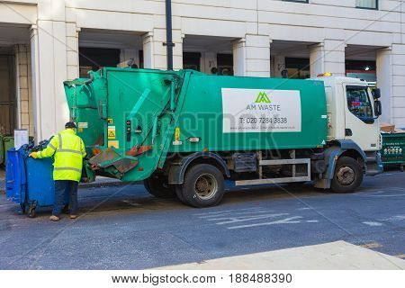 London England - 10 April 2017 - Garbage collector operates his lift to load the trash from is container into his truck in London England on April 10 2017