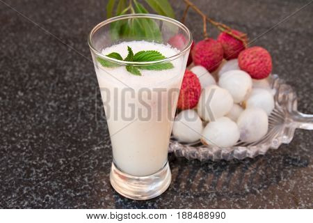Litchi juice in a glass. Fresh juicy lychee fruit on a glass plate. Organic leechee sweet fruit. Organic fruit concept. Exotic tropical litschi berry. Peeled lychee fruit.