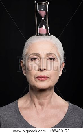 Senior Woman With Sand Clock On Head Isolated On Black