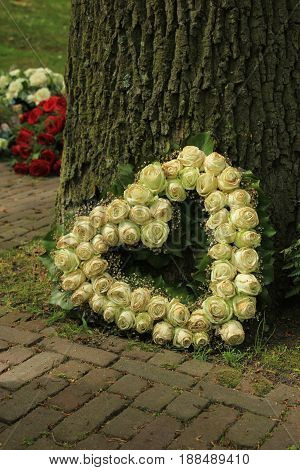 Heart shaped sympathy flowers or funeral flowers near a tree white roses
