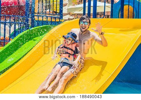 Father And Son On A Water Slide In The Water Park