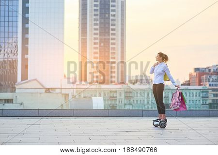 Woman riding hoverboard, shopping bags. Young female on city background. Buy and spend.
