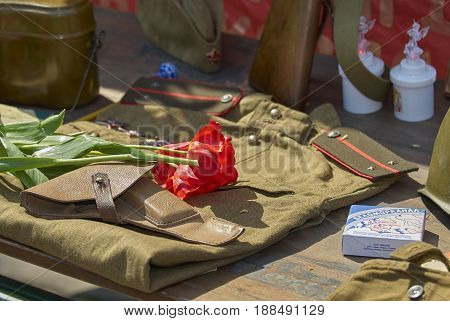MOSCOW, MAY 9, 2010: USSR WWII soldier khaki uniform, gun holster, flowers, old cigarettes with soviet machine gun, rifle. On celebration of Great victory 65th anniversary. USSR 9 May Victory day