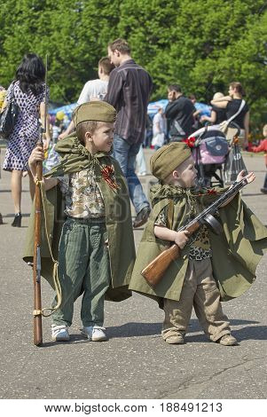 MOSCOW, MAY 9, 2010: Two young boys brothers in green USSR WWII uniform with soviet machine gun, rifle on celebration of Great victory 65th anniversary in Gorky Park garden. USSR  9 May Victory day