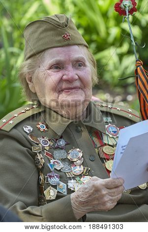 MOSCOW, MAY 9, 2010: Veteran solder woman portrait with medals on green uniform on celebration of Great victory 65th anniversary in Gorky Park. USSR victory in Second World War. 9 May Victory day