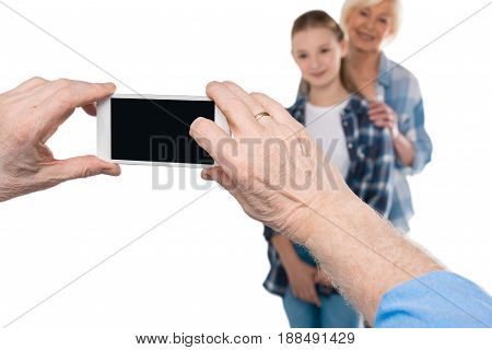 Grandfather Taking Photo Of Grandchild And Grandmother Isolated On White