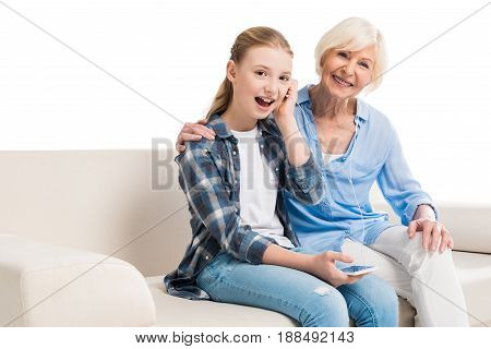 grandmother and grandchild listening music and sitting on sofa isolated on white
