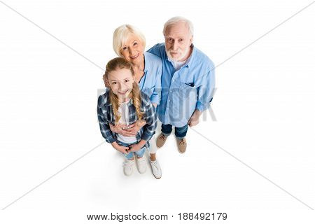 Overhead View Of Happy Grandfather, Grandmother And Grandchild Hugging And Looking At Camera Isolate