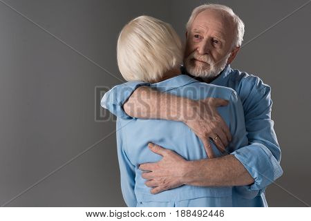 Caucasian Senior Couple Embracing Isolated On Grey In Studio